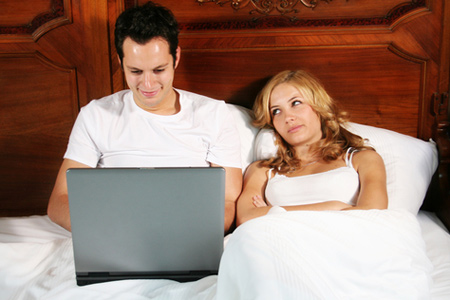 frustrated woman in bed with man and his laptop
